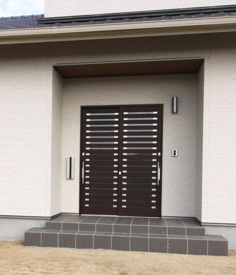 玄関には埋め込みのポストを設置、落ち着きのある色味の玄関は引違い戸です