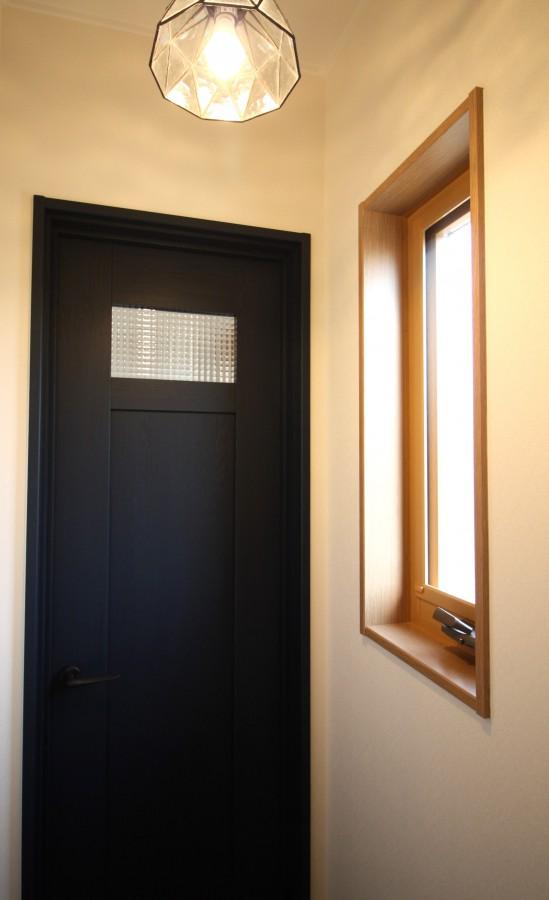 トイレにはネイビー色の扉を採用、アンティーク調の照明器具との相性ばっちりです